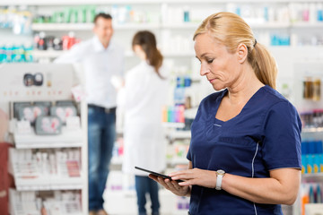 Female Assistant Holding Digital Tablet At Pharmacy