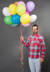 Handsome hipster man with multi-coloured baloons in studio