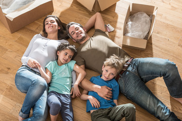 family laying on the wooden floor of their new flat