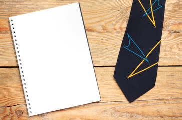 Tie and notepad on a wooden table