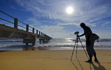 Silhouette of a photographer shooting the wooden bridge after su