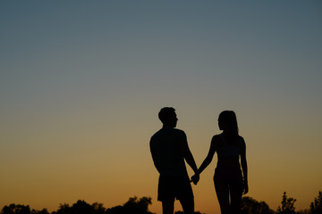 In love couple walking on sunset background.