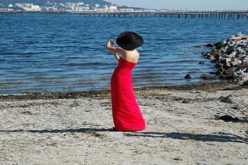 Femme élégante en rouge et noir photographie la mer avec son téléphone