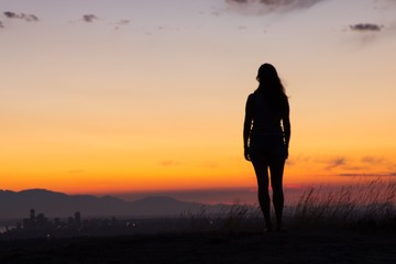 Girl silhouette in front of colorful sky