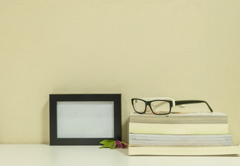 Frame for a photo with glasses on books background