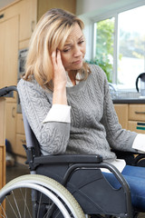 Depressed Woman Sitting In Wheelchair At Home