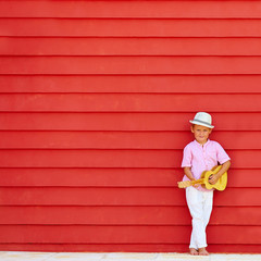 cute kid with ukulele play music near the colorful wall