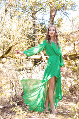 beautiful sexy girl Queen with bright makeup in a long dress with a crown on his head busick walks in the forest in bright Sunny summer day