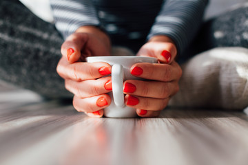 Woman warms his hands on a hot cup of coffee
