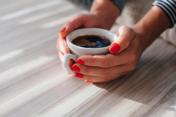 Closeup of woman holding coffee on the floor