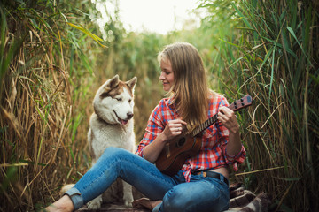 young caucasian woman playing ukulele. Female with siberian husky dog playing guitar outdoors