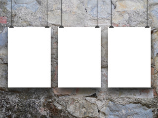 Three hanged paper sheets with clips on medieval stone wall background