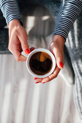 Woman holding a hot cup of coffee