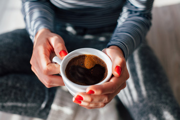 Woman with red nails holding a hot cup of coffee