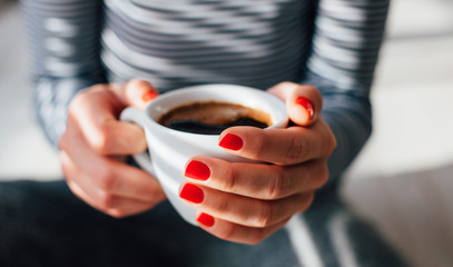 Closeup of woman with red nails holding coffee