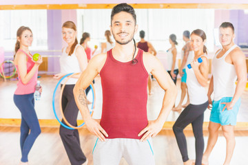 Happy handsome man with group peolpe in fitness class