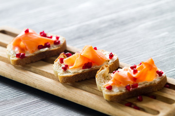 Salmon bruschetta with white cheese and pomegranates on wooden kitchen board over dark wooden background