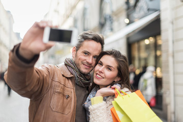 Trendy couple taking selfies with their smartphone in the city