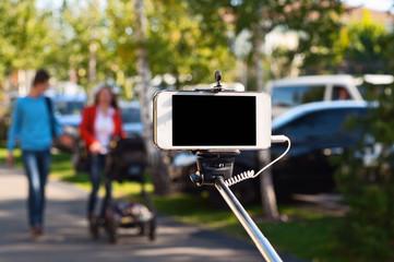 white phone in selfie stick