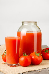 Tomato juice in glass and two-liter jar