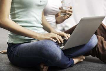 close up of young women holding a glass of water and sit on the floor while using her laptop