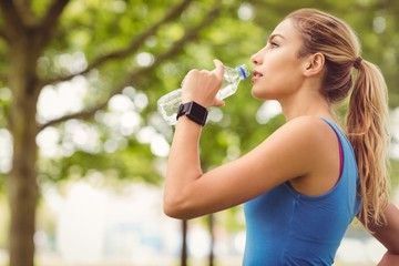 Jogger woman drinking water in park