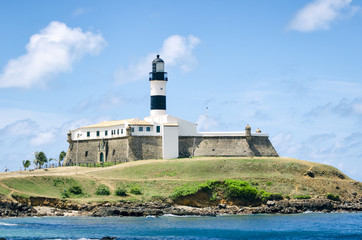 Portrait of the Farol da Barra lighthouse under clear blue sky in Salvador, Bahia, Brazil