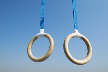 Traditional wooden gymnast rings hanging from blue straps in clear blue sky