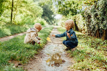 Happy little boy and girl playing with leaves in a puddle