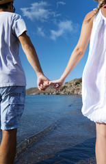 Young couple is walking on the beach hand to hand