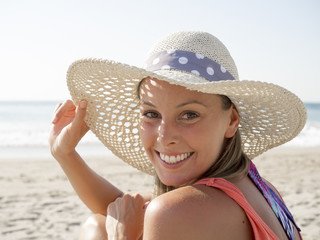 happy girl smiling portrait in the beach  wearing a  hat with the sea and horizon in the background