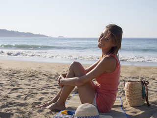happy pretty woman smiling  in the beach  wearing a pink top, she have a beach bag, hat, a suncream, the sea and horizon in the background