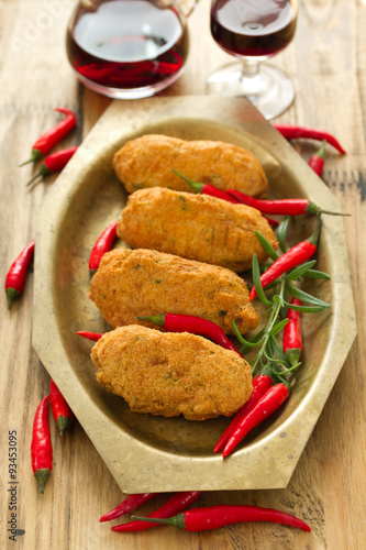 Cod fish croquettes with pepper on dish with red wine for Red wine with fish