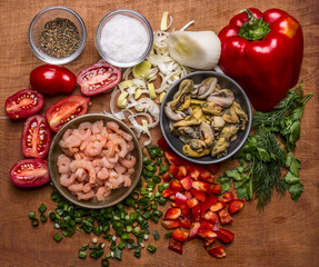 ingredients for cooking seafood shrimp and mussels cherry tomatoes seasoning salt chopped red pepper chopped onion parsley on wooden rustic background close up top view
