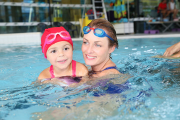 Mother and daughter training at the swimming-pool