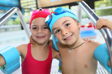 Portrait of cute little kids at the swimming-pool