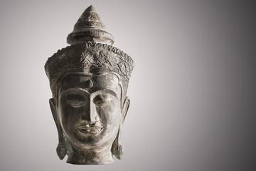 Antique brass buddha sculpture on illuminated black and white ba