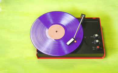 hipsters retro turntable with purple colored vinyl record, free copy space