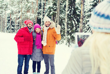 smiling friends with tablet pc in winter forest