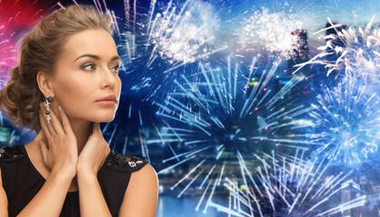 beautiful woman wearing earrings over firework