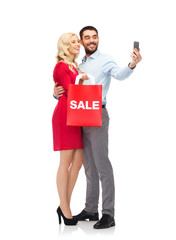 happy couple with smartphone and shopping bag