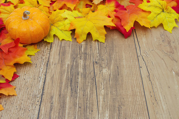 Autumn Leaves and Pumpkin on a Weather Wood Background