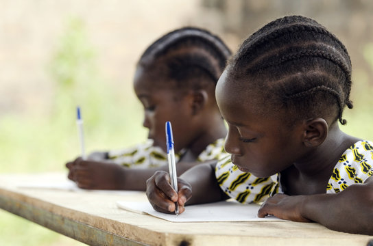 African Children at School Doing Homework. African ethnicity students writing their essay in an African school. They're holding blue pens to write down their homework whilst sitting in their desk.