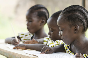 Two beautiful African girls and one African boy reading and writing at school as an educational symbol outside their school in Bamako, Mali. Beautiful education symbol background. Wall mural