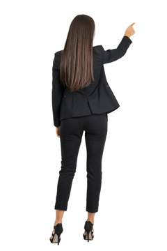 Rear view of long dark hair beauty pointing or presenting on her right side isolated