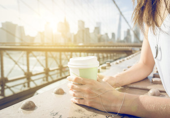 Close up on a woman holding coffee paper cup on Brooklyn bridge in New york