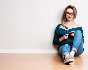 Young blonde woman relaxing on floor at home reading book.