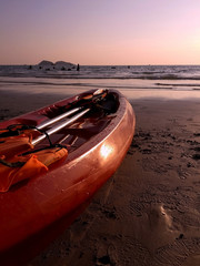 red kayak with paddle and life vest