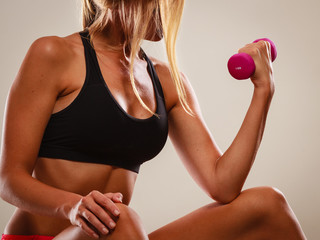 Strong fit woman exercising with dumbbell.