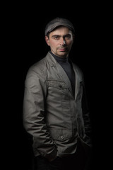 Serious man in jacket and cap on a black background holding hands in pockets